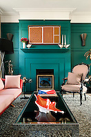 In the living room, the painted wooden panelling was inspired by the Georgian period and painted in a teal colour by the Paint and Paper Library. The 1960s Danish sofa was given a fresh appearance with with fabric by New Zealand based Mokum and the late 19th century chair is covered with stripy fabric by Donghia.