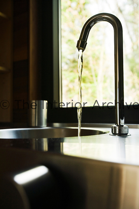 A bathroom is fitted with a stainless steel wash basin beneath a picture window