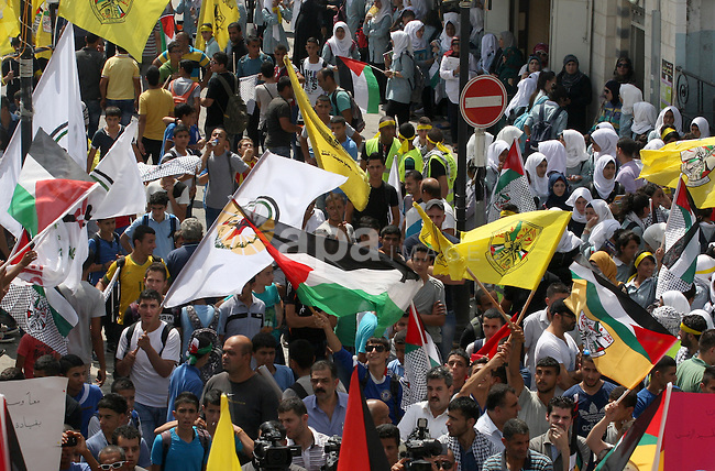 Palestinian supporters of Fatah movement hold the movement's flags during a protest marking the 48th anniversary of the Sabra and Shatila massacre in 1982, in the West Bank city of Nablus, September 16, 2014. The Sabra and Shatila massacre was the slaughter of between 762 and 3,500 civilians, mostly Palestinians and Lebanese Shiites, by the Kataeb Party, a Lebanese Christian militia, in the Sabra neighborhood and the adjacent Shatila refugee camp in Beirut, Lebanon. On 15 September, 63 Palestinian were individually identified and killed by an Israeli unit called Sayeret Matkal, and on 18 September 1982 a more widespread massacre was carried out by a Lebanese Christian Phalangist militia. Photo by Nedal Eshtayah