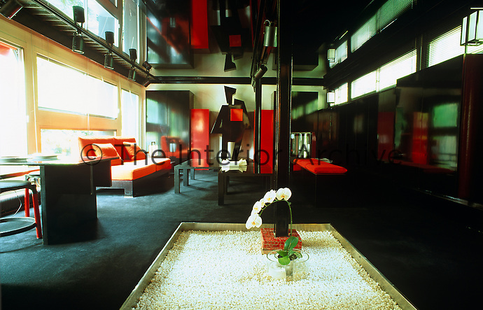 The living room continues the red and black colour scheme and has a tray of white gravel at its centre