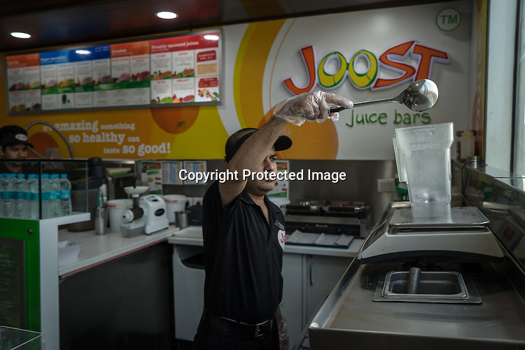 30 year old Haidar Ali, a deaf employee makes juice for a customer at Joost, a juice bar in a fitness club in New Delhi, India.