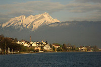 Beckenreid homes with snowcapped mountains in the background overlooking the lake Stätter See, Beckenreid, Luzern area, Switzerland.