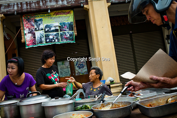 Locals buy take-away food from an open air street market in the UNESCO heritage city of Georgetown in Penang, Malaysia. Photo: Sanjit Das/Panos