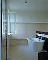 The free-standing bath sits next to a low floating wall separating it from the rest of the bathroom