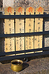 Kyoto City, Japan<br /> Adashino Nenbutsu-ji Temple, wooden prayer tablets offered on the stone base of a Buddha
