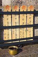 Kyoto City, Japan<br /> Adashino Nenbutsu-ji Temple, wooden prayer tablets offered on the stone base of a Buddha