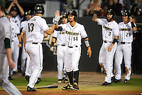 UCF Knights left fielder Bryce Peterson (13) high fives Matthew Mika (14) after scoring a run during a game against the Siena Saints on February 17, 2017 at UCF Baseball Complex in Orlando, Florida.  UCF defeated Siena 17-6.  (Mike Janes/Four Seam Images)