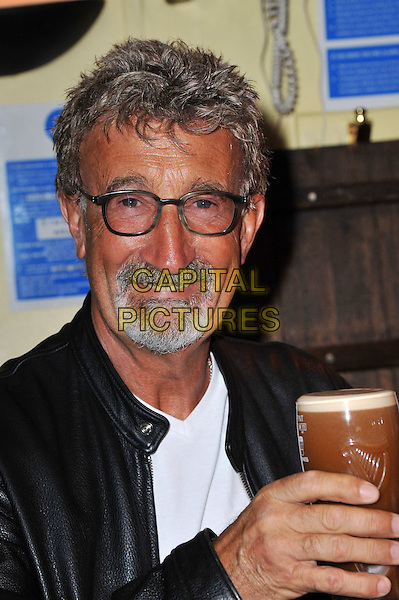 Eddie Jordan .Charismatic Formula 1 personality Eddie Jordan overjoyed with an honorary OBE in recognition for his services to charity and motor racing and drinks a celebratory pint of Guinness at the Toucan Bar, Soho, London, England..March 28th, 2012.headshot portrait glasses goatee facial hair drink beverage alcohol white black leather jacket .CAP/BF.©Bob Fidgeon/Capital Pictures.