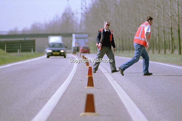 """Foto: VidiPhoto..BEMMEL - Rijkswaterstaat heeft maandag en dinsdag de kapotgereden rubberen flappen op de op- en afrit naar de A15 bij Bemmel vervangen. Dankzij de .reflecterende flappen is het aantal verkeersongevallen de afgelopen jaren op deze """"dodenweg"""" fors afgenomen. De A15 gaat op die plek over van vier naar .twee banen. Veel automobilisten hadden dat niet door en haalden toch in, met tal van (dodelijke) ongevallen als gevolg."""