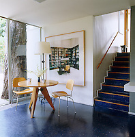 In the dining area a print by Candida Hofer hangs on a wall next to a Jean Prouve table and Eames dining chairs
