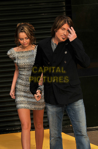 "MILEY CYRUS & BILLY RAY CYRUS .Attending the UK Film Premiere of ""Hannah Montana: The Movie"" at the Odeon cinema Leicester Square, London, England, UK, April 23rd 2009..half length silver grey gray beaded dress   shoulders shoulder pads structured sculpted bangles bracelets ring rings cuff black shirt jacket dad father daughter hand holding hands jeans .CAP/PL.©Phil Loftus/Capital Pictures"