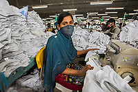 Thousands of women like Sujo migrate from rural villages to work in the 5,000 garment factories in the city of Dhakha. Since the collapse of the Rana Plaza factory in 2013 managers have been under pressure to create safer conditions for their workers, including fire safety and healthcare. This factory supplies clothing chains like H&M, Zara and Marks & Spencer. Sujo earns about $100 a month working as a sewing machine operator. She is recently married and her husband also works here.