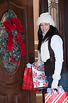 USA, Illinois, Metamora, mid adult woman holding Christmas presents entering house