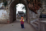 young boy at entry to village of ancient town Dachang along the Daning River, Lesser Three Gorges in rural China, Asia, 2003