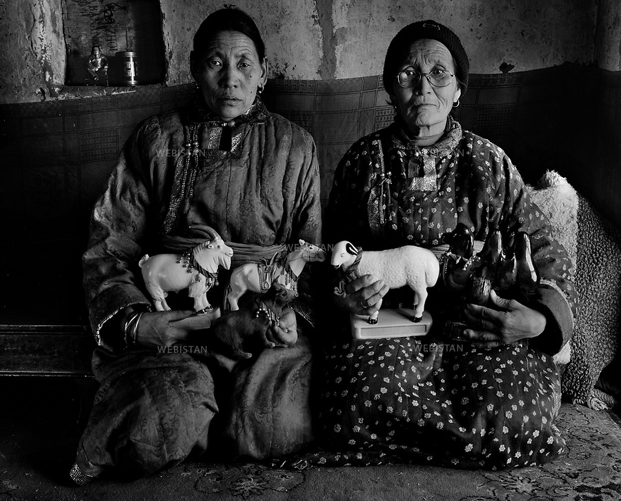 Inner Mongolia, Xilingol Meng, East Ujimqin Qi, Daotecuo'er Town, Bayintuga Gacha, March 2007.Aotegen (age 70) and Sema (age 58)...Aotegen (right) and her cousin Sema are photographed holding sculptures of the Five Animals in their hands..The nomadic Mongolians' symbolic Five Animals are the camel, horse, ox, sheep and goat..The origin and evolution of the Mongolian traditional animals interact with the long-term evolution of the ecological environment of the Mongolian plateau grasslands, and are closely related to the modes of production, living customs and cultural preferences, as well as the socio-political, economic and military systems of the Mongolian people. Nomadic Mongolians have domesticated the animals, and have always depended on them to build a better life. Even though many of them have changed their way of living in livestock farms by entering industrial cities, the Five Animals will still remain important to them. .Over 40 countries in the world are engaged in grassland animal husbandry, among which the majority choose 2 to 3 different animals for stock breeding. By contrast, only nomadic Mongolians have combined 5 kinds of animals, obtaining the most benefits from all species which provide excellent diversity for livestock farming..