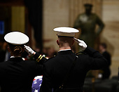 Members of the military salute near the flag draped casket of former President George H.W. Bush in the Capitol Rotunda in Washington, DC, December 3, 2018. - The body of the late former President George H.W. Bush will travel from Houston to Washington, where he will lie in state at the US Capitol through Wednesday morning. Bush, who died on November 30, will return to Houston for his funeral on Thursday. (Photo by Brendan SMIALOWSKI / POOL / AFP)