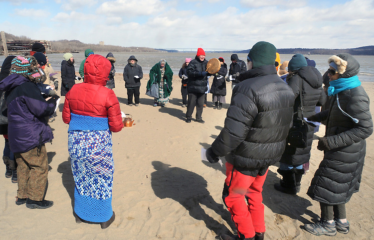 Etaoqua (Mahicanu), wearing green shawl, and, Nick Miles (Pamunkey, Powhatan), wearing red hat, representing the Assn of Native American of the Hudson Valley, seen leading a Native American Water Blessing Ceremony held for the Hudson River at Kingston Point Beach in Kingston, NY, on Saturday, March 4, 2017. Photo by Jim Peppler; Copyright Jim Peppler 2017