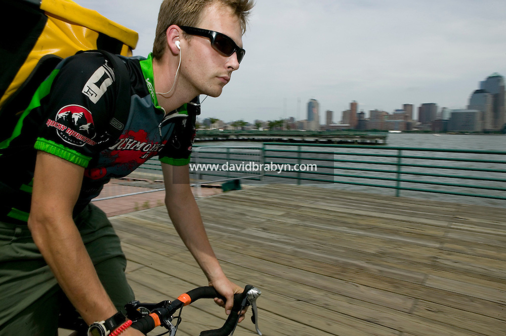 2 July 2005 - Jersey City, NJ, USA - A rider cycle along the waterfront with the Manhattan skyline in the background ahead of a qualifying race for the 13th annual cycle messenger world championships, Jersey City, USA, July 2nd 2005. More than 700 riders from all over the world took part in the 4-day competition which carries event based on the daily work of a city bike messenger.