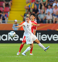 Heather O'Reilly (l) of Team USA and Paek Sol Hui of Team North Korea during the FIFA Women's World Cup at the FIFA Stadium in Dresden, Germany on June 28th, 2011.