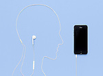 Man head outline made by a headphone cord plugged into iPhone 5s smartphone. Creative music concept on blue background.