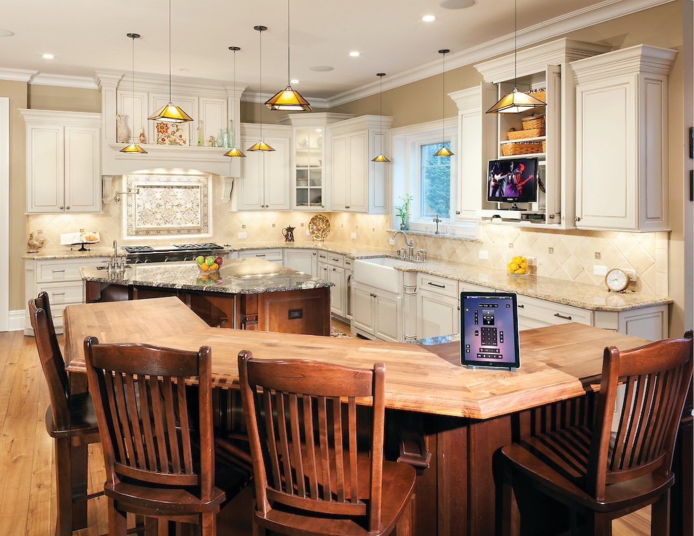 Elegant Chef's Kitchen with gorgeous white cabinetry and hidden TV.