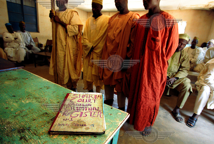 "photo: Sven Torfinn.Nigeria, Kano, Kano State, october 2002.Sharia court, on the table a book with the title ""Sharia Court Criminal Register"", in the background four men are heard in a family dispute concerning an inheritance issue..Sharia law was working on a community / local level and has been practised already hundreds of years in Northern Nigeria, but in recent years declared official jurisdiction in several northern states of Nigeria. But sentences /.verdicts by the national sharia courts such as stoning to death and amputations / choping of hands because of theft are getting now a lot of media attentions and critisism from different western organizations and goverments."