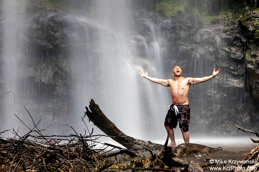 Local Hawaiian looking shirtless man standing with arms spread beneath Waimoku Falls waterfall on Maui in Hawaii