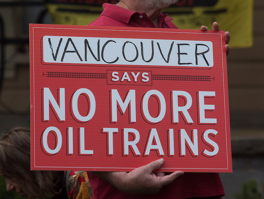 A protester stands with a sign and listens to speeches in Esther Short Park in Vancouver Monday July 18, 2016. Demonstrators opposing the Vancouver Energy oil terminal rallied at the park and marched down to nearby train tracks ahead of a city council meting. (Photo by Natalie Behring/ for the The Columbian)