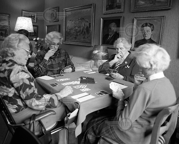 A group of elderly women play bridge.