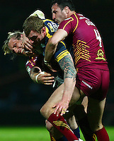 PICTURE BY VAUGHN RIDLEY/SWPIX.COM - Rugby League - Super League - Leeds Rhinos v Huddersfield Giants - Headingley, Leeds, England - 30/03/12 - Leeds Jamie Peacock is tackled by Huddersfield's Eorl Crabtree and Lee Gilmour.