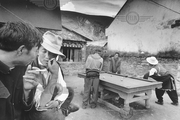 © Tim Dirven / Panos Pictures..Litang, Sichuan Province, CHINA..Young Tibetan men playing pool and smoking cigarettes during the annual Buddhist festival at the monastery of Litang.