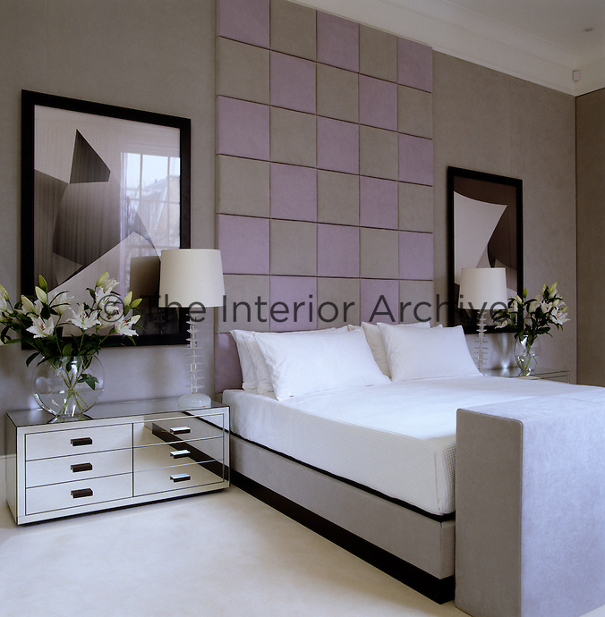 The walls of this bedroom are covered in suede and the platform bed is flanked by a pair of low mirrored chests of drawers