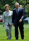U.S. President George W. Bush, walks with First Lady Laura Bush after returning from Camp David, to deliver a statement to the press on the death of his former press secretary Tony Snow, on the South Lawn of the White House  in Washington, DC on 13 July 2008. Snow, the former Fox News anchor died Saturday after a battle with colon cancer. He was 53.<br /> Credit: Matthew Cavanaugh / Pool via CNP