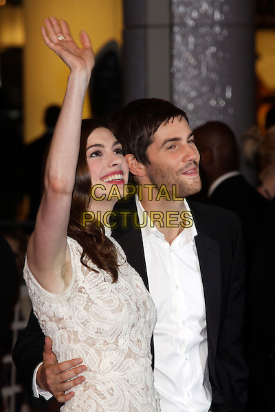 "ANNE HATHAWAY (in Alexander McQueen) & JIM STURGESS .""One Day"" UK premiere, Vue Westfield cinema, Westfield Shopping Centre, London, England..August 23rd, 2011.half length white sleeveless crochet lace dress white embroidered shirt black suit arm in air waving tongue funny profile stubble facial hair arm around waist.CAP/AH.©Adam Houghton/Capital Pictures."