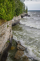 Waves from Lake Michigan breaking at Cave Point County Park in Door County Wisconsin.  The waves have eroded the bank and created sea caves under the cliffs.