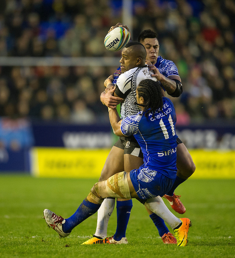 Fiji's Akuila Uate looks to off load the ball as he is tackled by Samoa's Iosia Soliola <br /> <br /> Photo by Stephen White/CameraSport<br /> <br /> 2013 Rugby League World Cup - Quarter Final - Samoa v Fiji - Sunday 17th November 2013 - Halliwell Jones Stadium - Warrington<br /> <br /> &copy; CameraSport - 43 Linden Ave. Countesthorpe. Leicester. England. LE8 5PG - Tel: +44 (0) 116 277 4147 - admin@camerasport.com - www.camerasport.com