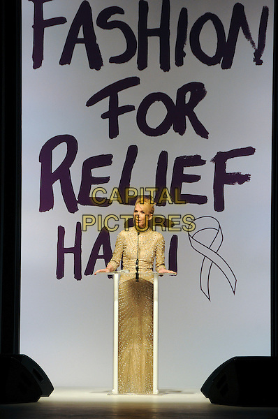 TRUDIE STYLER .The Fashion For Relief Haiti 2010 show for London Fashion Week Autumn/Winter 2010 at Somerset House, London, England..February 18th, 2010.LFW catwalk runway full length podium speech gold beige.CAP/CAS.©Bob Cass/Capital Pictures.