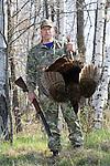 Hunter, holding shotgun, with harvested wild turkey