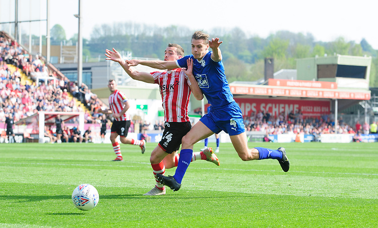 Lincoln City's Harry Toffolo vies for possession with Tranmere Rovers' Sid Nelson<br /> <br /> Photographer Chris Vaughan/CameraSport<br /> <br /> The EFL Sky Bet League Two - Lincoln City v Tranmere Rovers - Monday 22nd April 2019 - Sincil Bank - Lincoln<br /> <br /> World Copyright © 2019 CameraSport. All rights reserved. 43 Linden Ave. Countesthorpe. Leicester. England. LE8 5PG - Tel: +44 (0) 116 277 4147 - admin@camerasport.com - www.camerasport.com