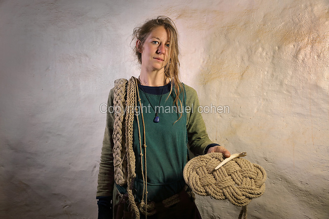 Elodie Michel, rope maker on the Guedelon project since 29/05/2012, wearing medieval costume and carrying lengths of rope and a rope mat, at the Chateau de Guedelon, a castle built since 1997 using only medieval materials and processes, in Treigny, Yonne, Burgundy, France. The Guedelon project was begun in 1997 by Michel Guyot, owner of the nearby Chateau de Saint-Fargeau, with architect Jacques Moulin. It is an educational and scientific project with the aim of understanding medieval building techniques and the chateau should be completed in the 2020s. Picture by Manuel Cohen
