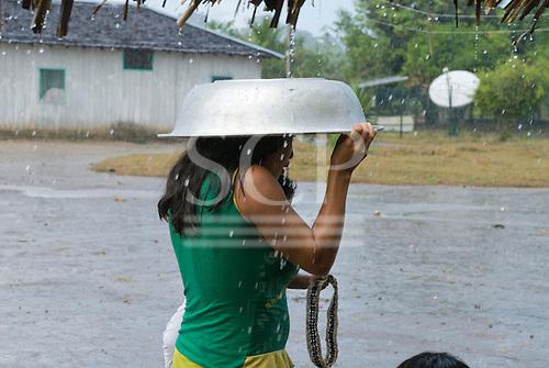 Pará State, Brazil. Aldeia Apyterewa (Parakana). Woman sheltering under an aluminium bowl in the rain.