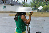 Pará State, Brazil. Aldeia Apyterewa (Parakana). Woman sheltering under an aluminium bowl in the rain.