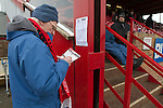 Altrincham 2 Worcester City 0, 23/03/2013. Moss Lane, Blue Square Bet North. A spectator copying down the team line-ups before the Blue Square Bet North fixture between Altrincham and Worcester City at Moss Lane, Altrincham. The home team won the match 2-0 watched by 777 spectators on a day when most non-League football in England was cancelled due to adverse weather. Altrincham were historically one of the major English non-League teams but have never been promoted to the Football League. Photo by Colin McPherson.