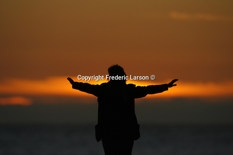 A woman faces the setting sun on Rodeo Beach at Fort Cronhkite Beach in Marin County, California.
