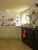 The simple kitchen is equipped with a large black Aga
