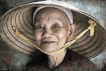 An elderly oriental woman smiles from under her hat.