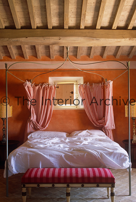 The red and white striped curtains that hang from the wrought-iron frame of this four-poster bed echo the upholstery of the striped bench