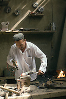 A metal worker hammers the steel that will become a Yengisar knife. Yengisar is a small city nearby Kashgar on the western tip of China and it has been producing these knives for over 400 years. Their secrets and techniques passed down from generation to generation. A Yengisar knife is one of the most important possessions for a Uyghur man and a popular tourist souvenir..