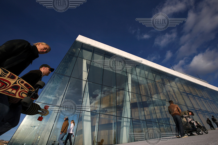 People walk past the Opera House in Oslo.