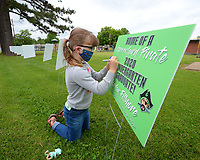 Jordan Fillmore, 5, uses a marker Saturday, May 16, 2020, to decorate a yard sign that bears her name as a kindergarten graduate while visiting Greenland Elementary School with her grandmother, Terry Reed. The privately funded signs will be on display through the weekend and then be available for decoration and pickup starting Monday. Students are also invited to share what they want to be when they grow up next week for a video project. Visit nwaonline.com/200517Daily/ for today's photo gallery.<br /> (NWA Democrat-Gazette/Andy Shupe)
